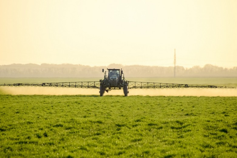 Tractor sprays weed killer on field