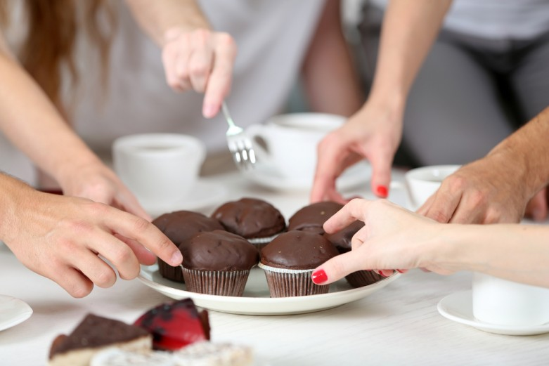 Chocolate muffins on plates, hands grasping