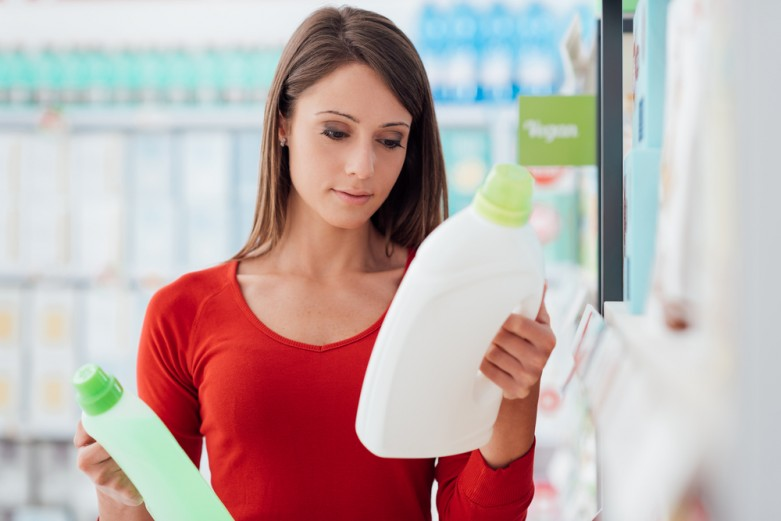 Woman has two kinds of detergent in her hand.