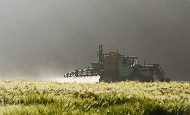 An agricultural machine puts spray on a field.