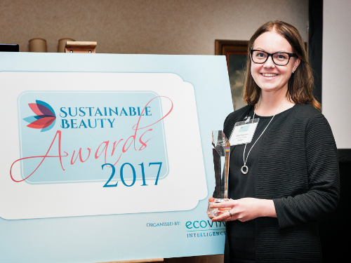 A woman standing next to a banner for the Sustainable Beauty Award.