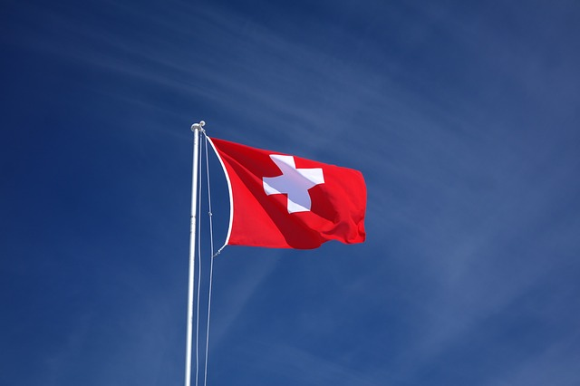 Swiss flag in front of blue sky