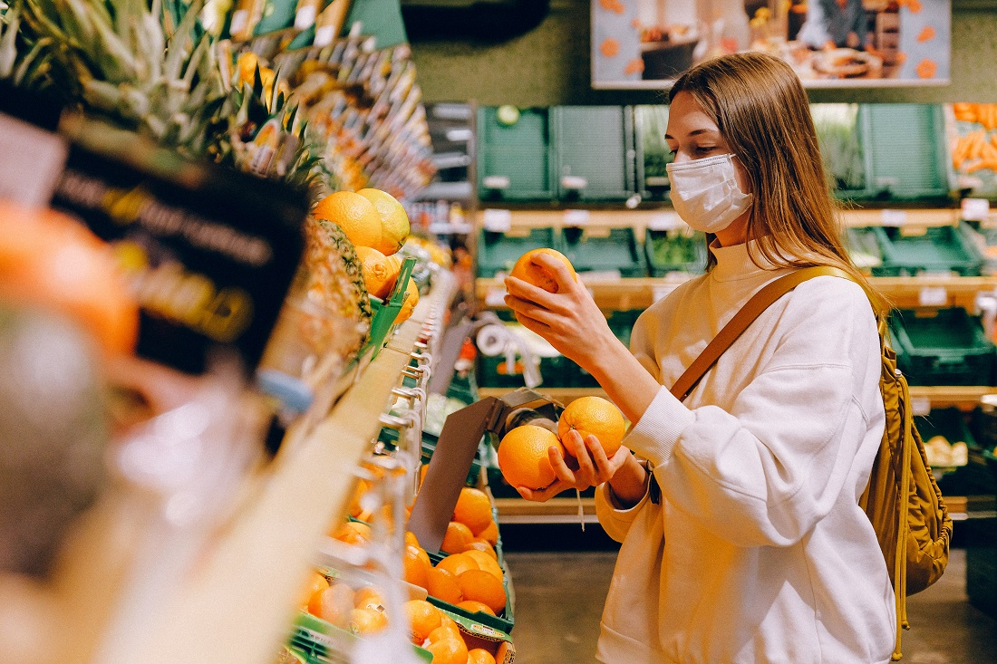 Woman with face mask buying fruit